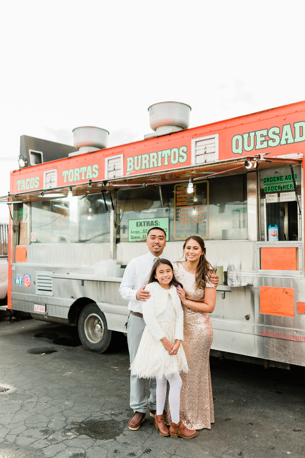 just married couple and their daughter in front of a taco truck